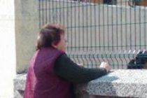 Възрастна жена търгува през ограда на Начално училище